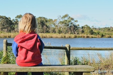 Lonely little blonde girl sitting on wooden bench with space on side and watching ducks in pond photo