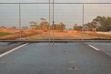 Metallic gates and lock on unfinished asphalt road to construction site with clay and sings in bright sunlight behind the fence Stock Photo