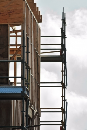scaffolds: New unfinished house with australian wooden frame and metal scaffolds against bright cloudy sky