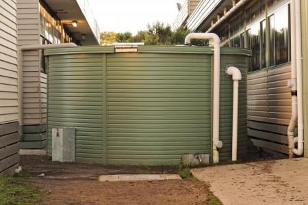 eau de pluie: Grand r�servoir vert collecte des eaux pluviales avec des tuyaux en provenance de toit utilis� en Australie