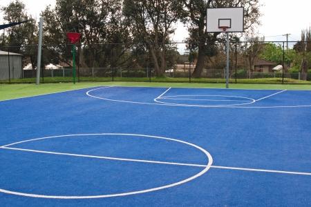 pasto sintetico: Centro de baloncesto en brillante verde y azul, superficie sint�tica alfombra de hierba con l�neas blancas y la cesta de formaci�n