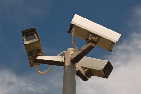 Three security outdoor cameras on metallic post with clouds and blue sky in background Stock Photo - 16248395