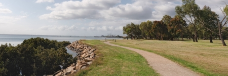 hastings: Winding gravel footpath at Hastings seashore with trees, clouds and boats in marina in Victoria, Australia