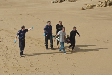 Paramedic in uniform points direction to group of surfers and another paramedic who carry injured surfer in a stretcher and walk on sand at Bells Beach, rocks in background, Victoria, Australia on December 15