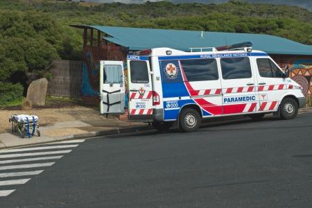 strand australie: Paramedicus ambulance auto met geopende deuren en bereid brancard geparkeerd op Bells Beach parking aan gewonde surfer te redden op 15 december, Victoria, Australië