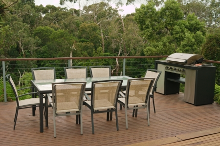 balconies: Open space terrace with wooden floor table, chairs and bbq with bush in background