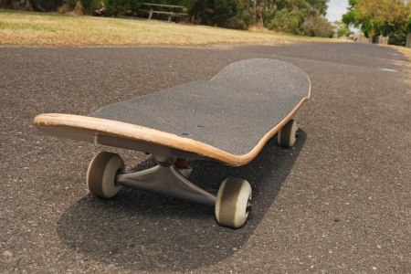 extreme angle: Skateboard on rough asphalt footpath at angle with trees and blue sky in background