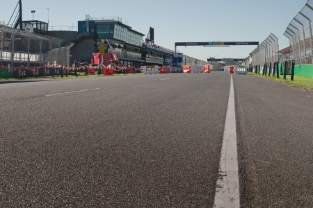 prix: White line at asphalt at construction zone near pit stop with workers, lifts and cranes at Melbourne Formula One Grand Prix
