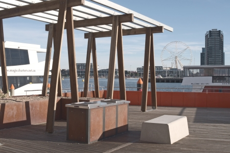 Public wooden BBQ area at Victoria Harbor promenade in Docklands with boats, Southern Star in Waterfront City and light clouds on blue sky in Victoria, Australia