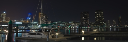 Night panorama at Victoria Harbor in Docklands with pier and catamaran moored in calm water and CBD lights in background in Victoria, Australia