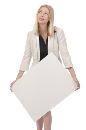 woman hands up: Blond woman in white business suit pretend to hold heavy white board in her hands and looking up, isolated on white