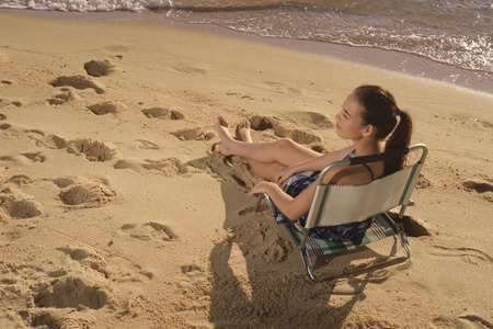 breaking waves: Young dark brown hair woman in sitting in chair in warm sunlight on sandy beach  with small breaking waves nearby