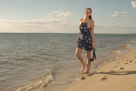 dark brown hair: Cheerful young dark brown hair woman walks on the edge of calm sea with high heels in her hands with blue sky and clouds in background