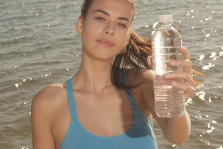 glare: Young woman with dark hair holds water bottle with glare Stock Photo