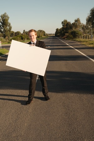message board: Happy businessman in black suit holds white billboard standing on road