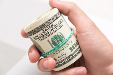 Un uomo tiene un mucchio di soldi, contorto in un mazzo e legato con un elastico verde su uno sfondo con texture leggera Archivio Fotografico - 85830489