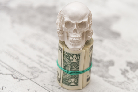 A skull standing on a bundle of money, twisted in a bunch and tied with a green rubber band