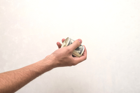 tosses: A man holds a bunch of money, twisted in a bunch and tied with a green rubber band on a light textured background Stock Photo