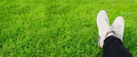 Female sneakers on legs in grass Stock Photo
