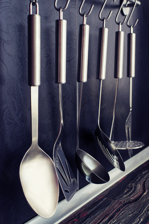 Black kitchen with kitchen hanging accessories on a tile background Stock Photo