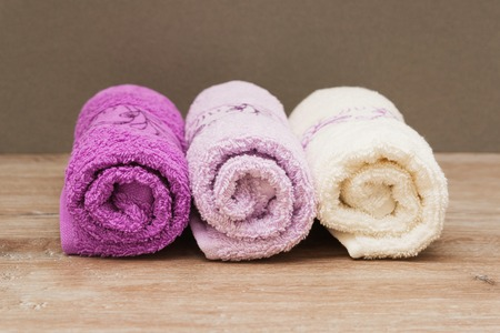 swimming candles: Multicolored towels on a wooden background lying next to each other