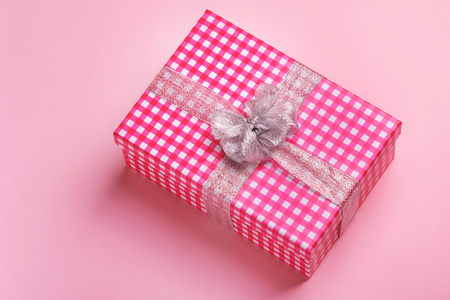 Gift box with a gray bow on a pink background