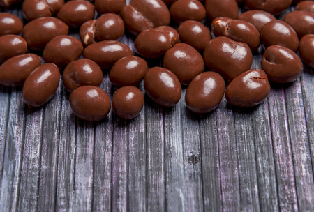 Peanuts in chocolate. Sweet peanut in the background. Wooden background. Place for text. A place for a label. Sweet peanuts in chocolate for tea and coffee.