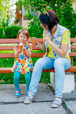 mother on bench: mother and daughter eating ice cream. Mom and daughter enjoy fun ice cream sitting  on the bench on summer vacation