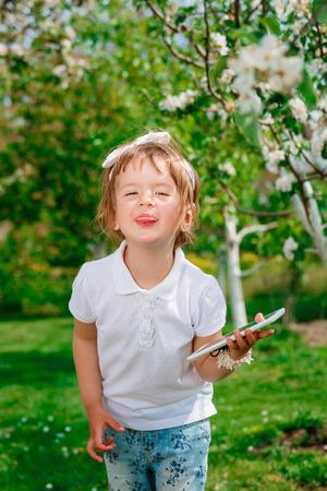 enfant qui joue: Bonne petite fille habillée en polo blanc et un jean, pieds nus debout avec la tablette dans le parc, montre la langue, Hamming. Petite fille l'aide d'une tablette.