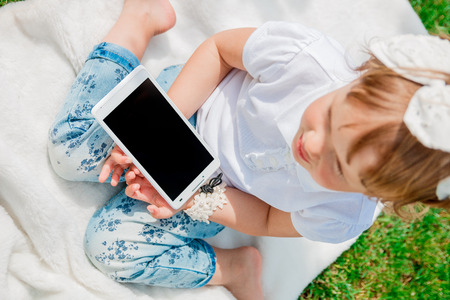 child hand: Unrecognizable Little baby girl with Tablet, dressed in white polo and jeans, barefoot sitting on the white cover in the park, top view