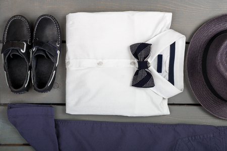 bow of boat: Mens outfit on wooden background. Kids fashion clothes. Grey fedora, navy pant, white shirt, black bow tie and boat shoes for boy. Top view.