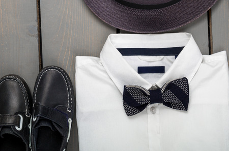 fedora: Mens outfit on wooden background. Kids fashion clothes. Grey fedora, white shirt, black bow tie and boat shoes for boy. Top view. Close up.