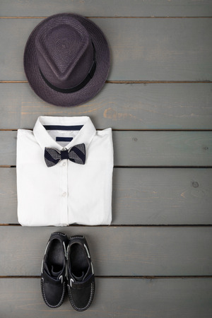 bow of boat: Mens outfit on wooden background. Kids fashion clothes. Grey fedora, white shirt, black bow tie and boat shoes for boy. Top view. Copy space. Frame