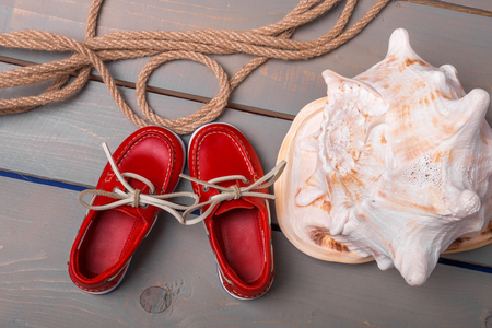 sports shell: Red boat shoes near big shell and rope on wooden background. Close up. Top view. Stock Photo