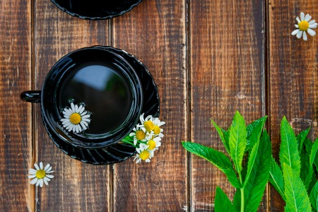 black cup of tea with chamomile near fresh mint on wooden table background. Tea concept. Frame, copy space. Top view.
