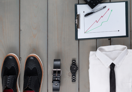 mans watch: Businessman, work outfit on grey wooden background. White shirt with black tie, watch, belt, oxford shoes, planchette and calculator. Back to work. Copy space, frame. Set of mans fashion and accessories. Stock Photo