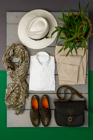 pant: Womens outfit on wooden background. fashion clothes. beige straw hat, beige pant, white shirt, green scarf black crossbody bag and oxford shoes near flower pot. Top view.