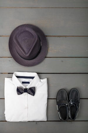 bow of boat: Mens outfit on wooden background. Kids fashion clothes. Grey fedora, white shirt, black bow tie and boat shoes for boy. Top view. Copy space.