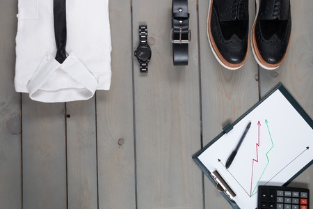 mans watch: Businessman, work outfit on grey wooden background. White shirt with black tie, watch, belt, oxford shoes, planchette and calculator. Back to work. Copy space, Set of mans fashion and accessories. Stock Photo
