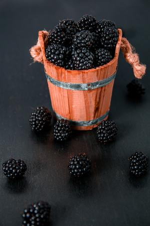 black raspberries: Black raspberries in a wooden basket and on black wooden table.