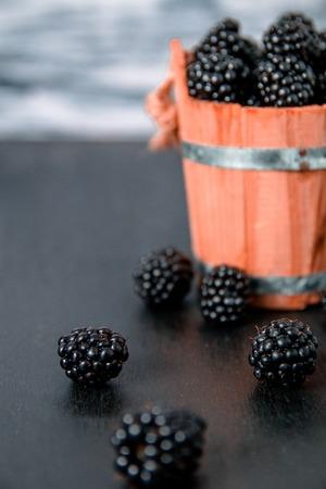 black raspberries: Black raspberries in a wooden basket and on black wooden table. Copy space. Stock Photo