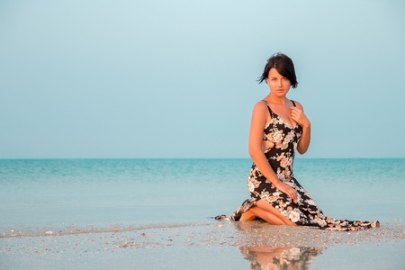 Woman in a floral dress sitting in shallow ocean water. Girl in the sea.  Looking in the camera.