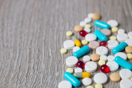 generic drugs: A lot of colorful medication and pills from above on grey wooden background. Copy space. Top view, frame. Painkillers, tablets, generic pills, drugs.