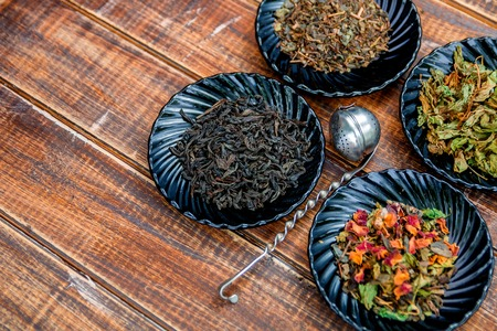 Different kinds of tea on plates near brown teapot on wooden background. Assortment of dry tea. Tea concept. Tea leaves.