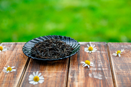 loose leaf: Dry Black tea on plate on wooden table with flowers of chamomile in garden and on nature background.Tea concept. Tea leaves. Closeup