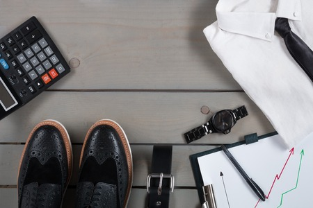 work belt: Businessman, work outfit on grey wooden background. White shirt with black tie, watch, belt, oxford shoes, planchette and calculator. Back to work. Copy space, frame. Set of mans fashion and accessories. Stock Photo