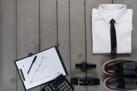 Businessman, work outfit on grey wooden background. White shirt with black tie, watch, belt, oxford shoes, planchette and calculator. Back to work. Copy space, frame. Set of mans fashion and accessories. Banco de Imagens - 62264082