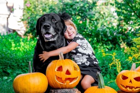 Víspera de Todos los Santos. Niño vestido de negro labrador cercano entre la decoración de la Jack-o-linterna, truco o. Niña con el perro cerca de la calabaza en la madera, al aire libre. Amor