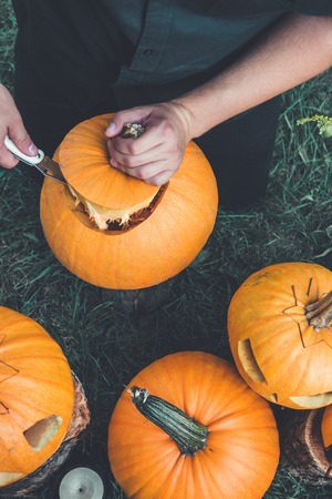 A close up of man's hand cuts a lid from a pumpkin as he prepares a jack-o-lantern. Halloween. Decoration for party.
