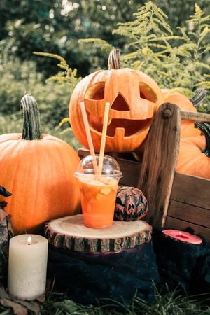 terrifying: Halloween cocktail with pumpkins decoration on background. Punch for a party. Jack-o-Lantern.